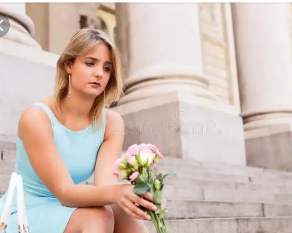 A sad lady holding flowers