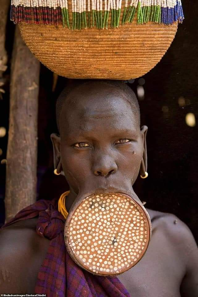 A mursi woman carrying a calabash on her head and a lip plate